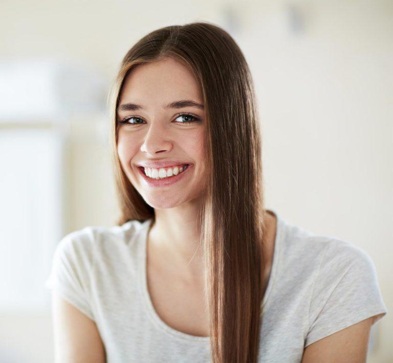 Junge Frau mit hübschen Zähnen schaut in die Kamera
