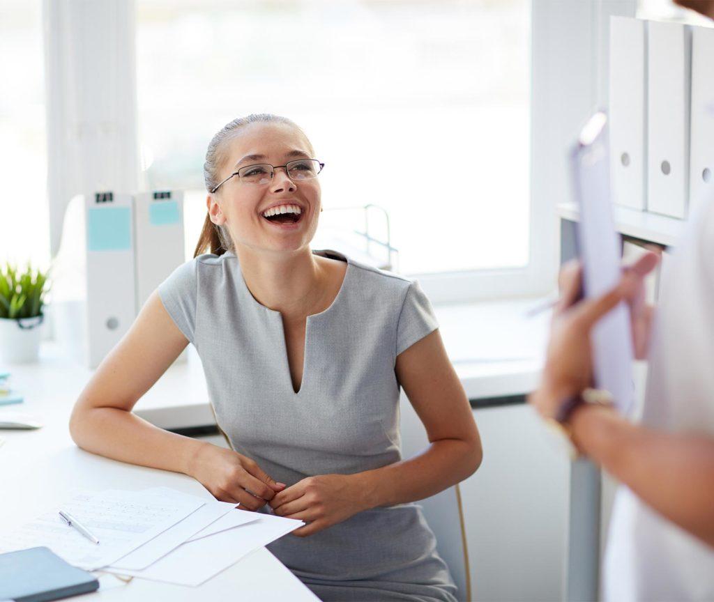 Junge Frau mit schönen Zähnen lacht in einem Dentallabor