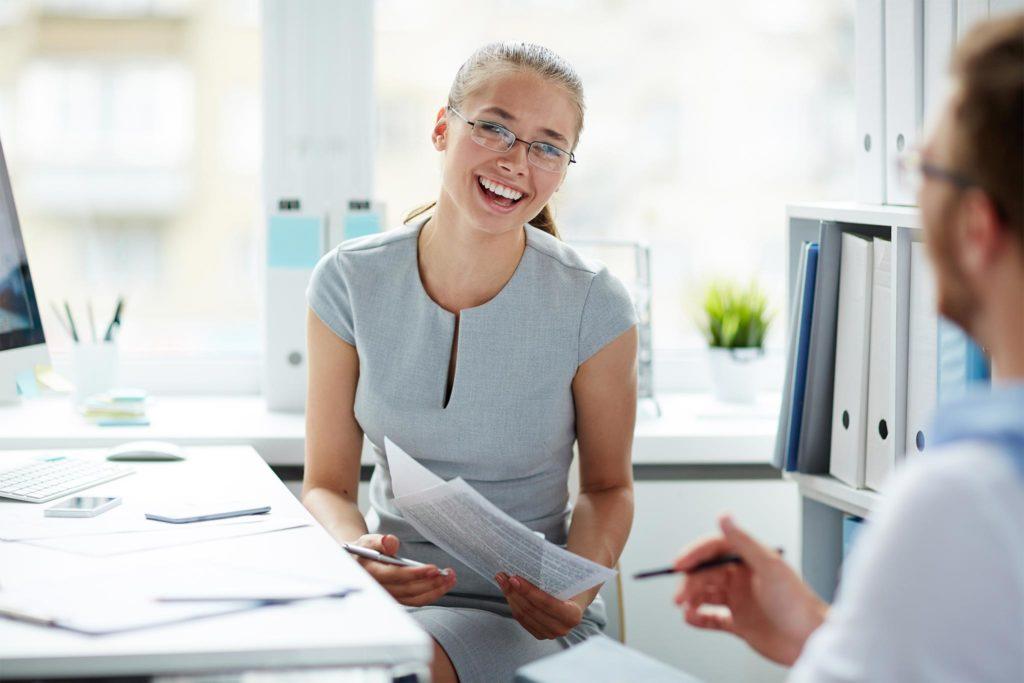 Junge Frau mit schönen Zähnen lacht in einem Büro