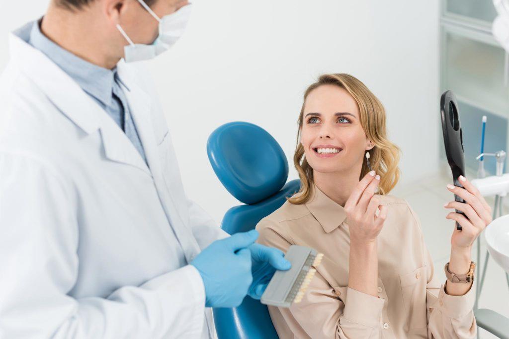 Frau mit schönen Zähnen hält Zahnimplantate in der Hand und schaut einen Zahnarzt an
