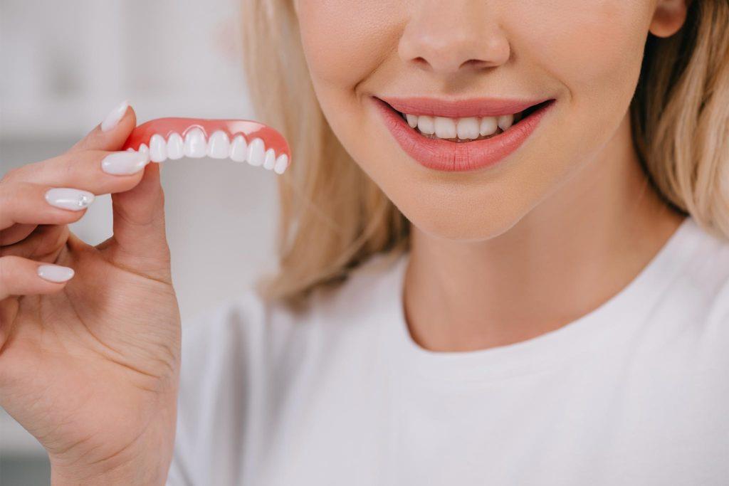 Frau hält ein Zahnersatz-Gebiss in der Hand