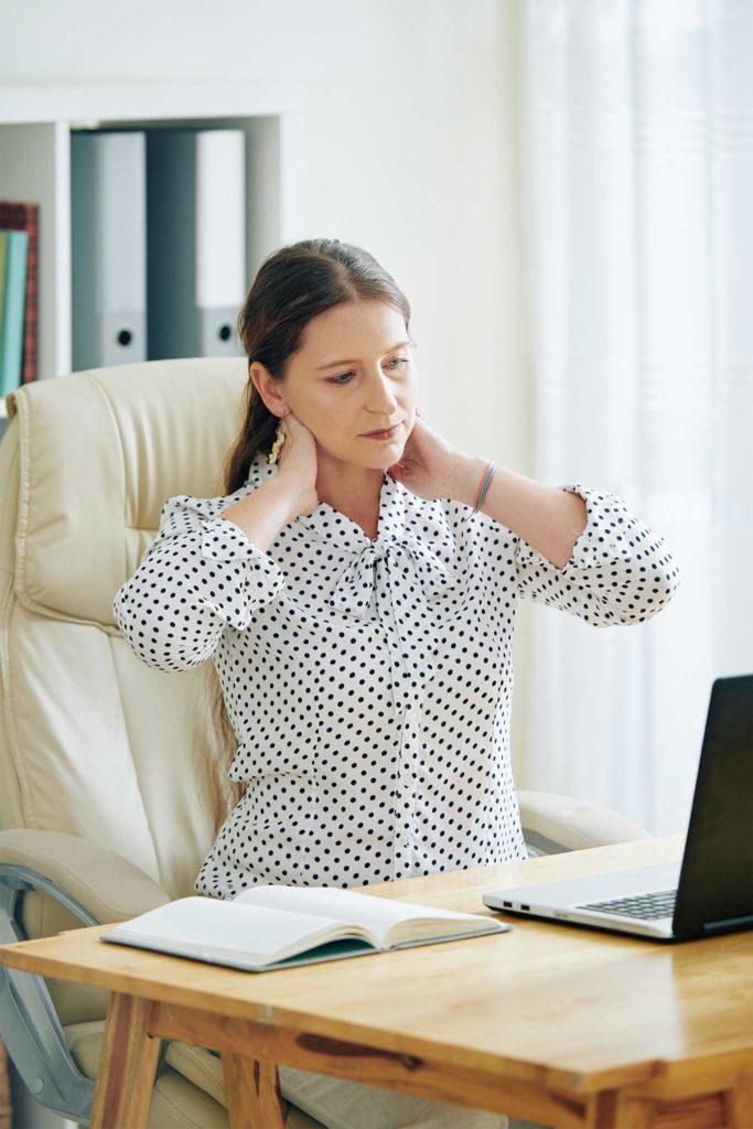 Geschäftsfrau fasst Sich an Ihren schmerzenden Nacken