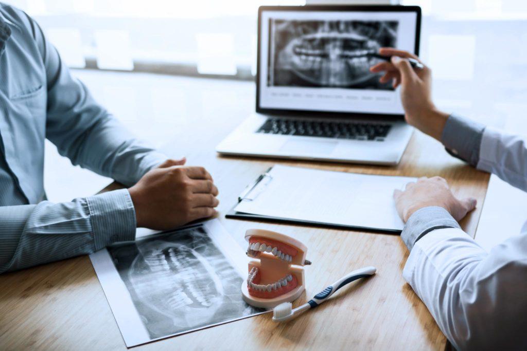 Zahnarzt und Zahntechniker unterhalten Sich am Laptop über ein Gebiss