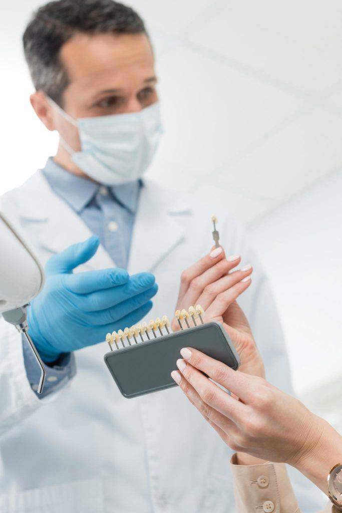 Zahnarzt zeigt einer Frau Farbvarianten von Zahnersatz