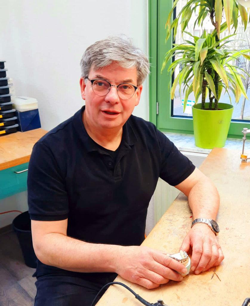 Mann in schwarzem T-Shirt hält einen Zahnersatz in den Händen