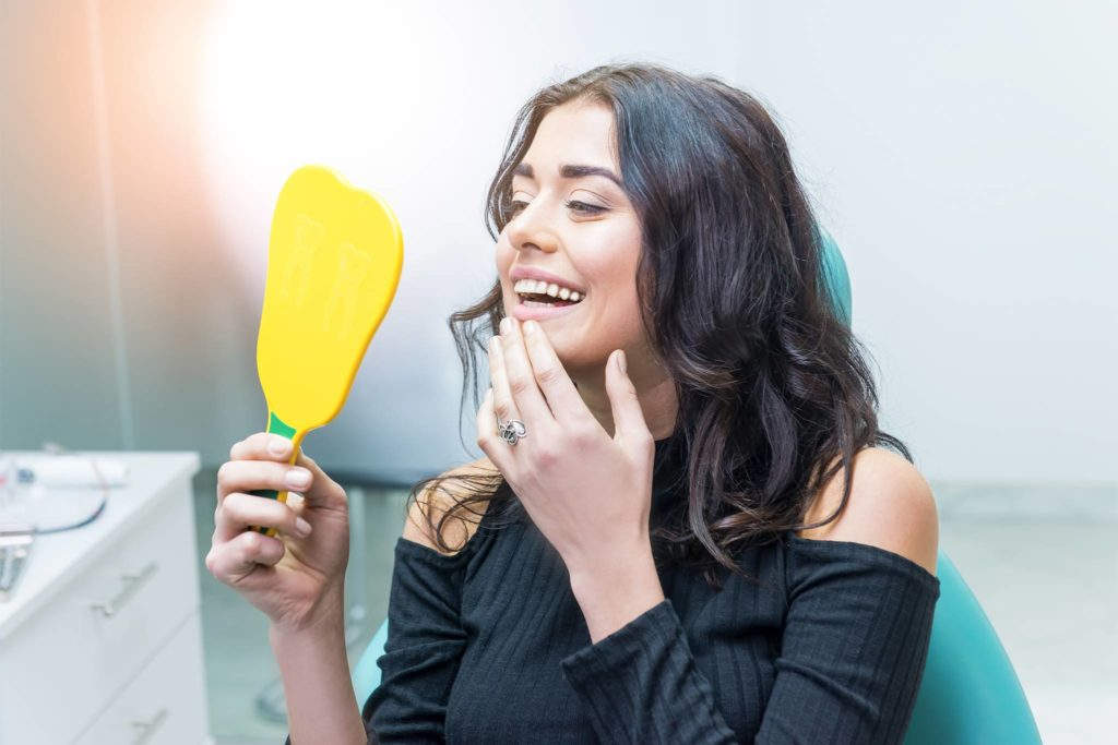 Junge Frau lächtelt mit schönen Zähnen in den Spiegel