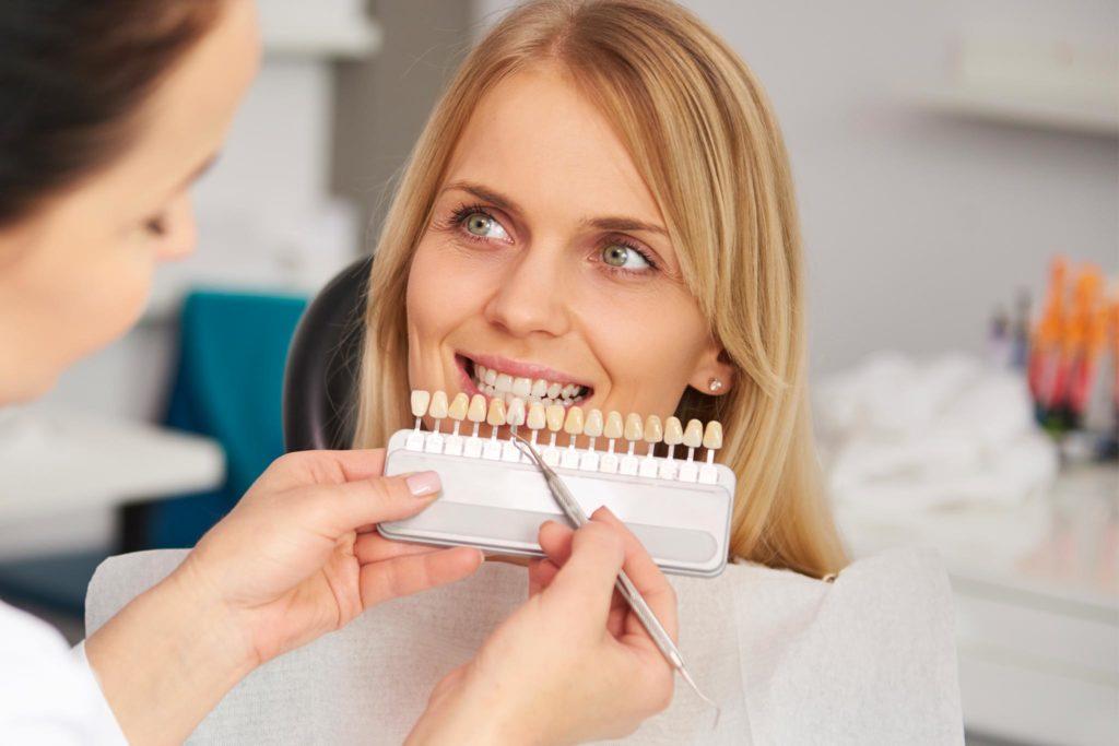 Frau mit schönen Zähnen bei der Farbabnahme eines Zahnes