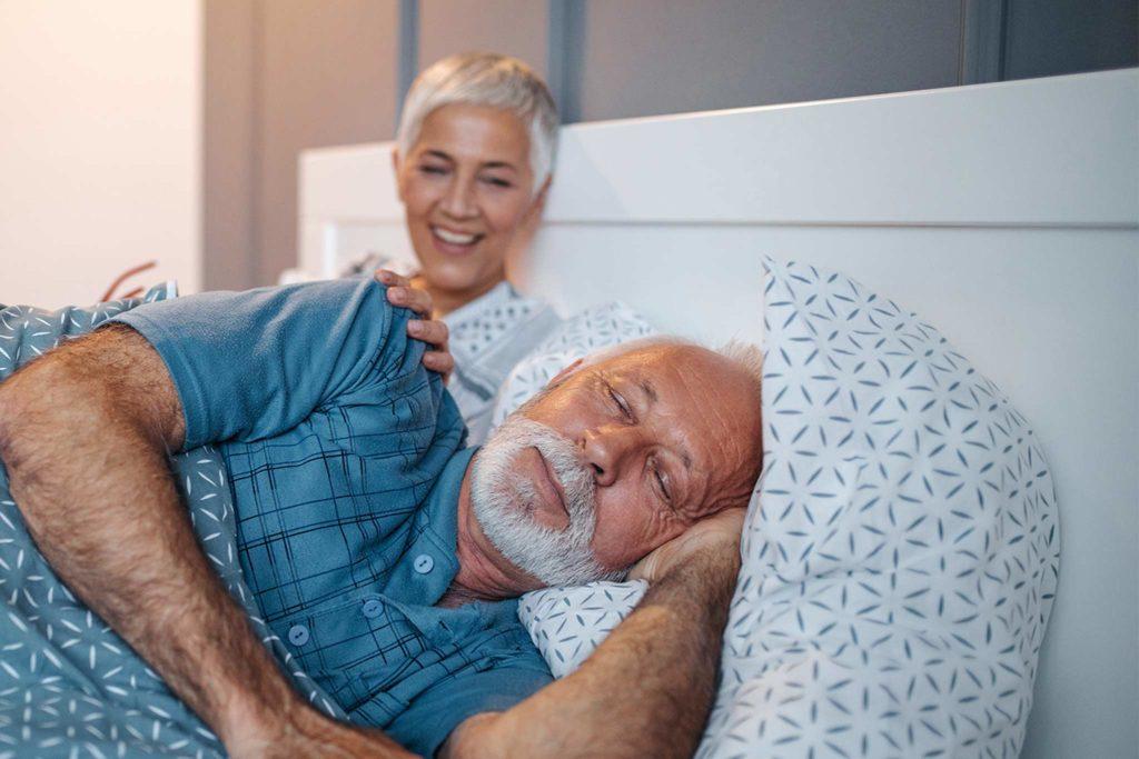 Mann schläft im Bett neben seiner sitzenden Frau